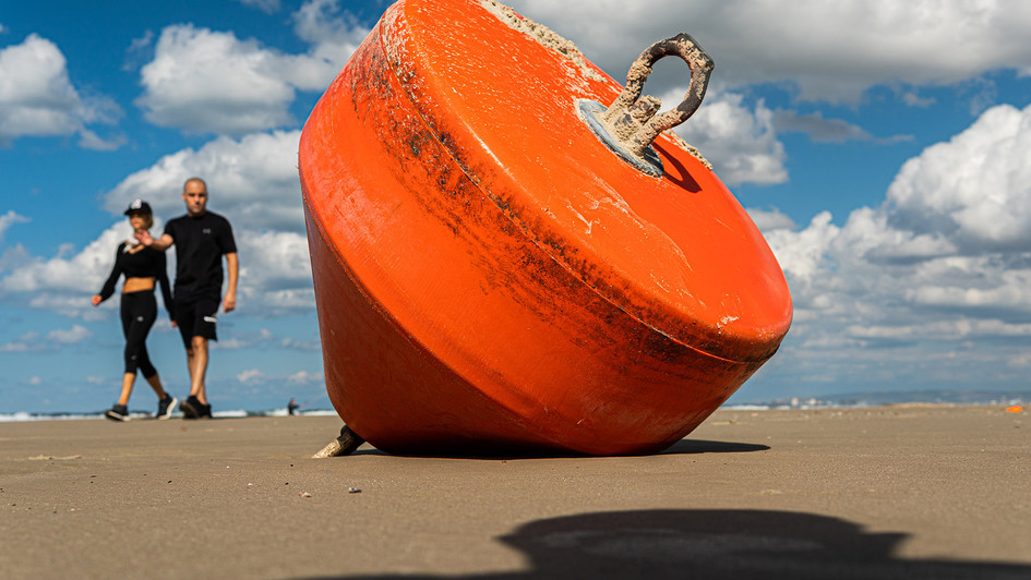 A couple walks at the beach near a buoy