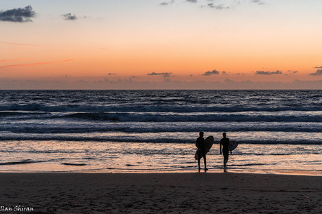 Two surfers getting out of the water at sunset time