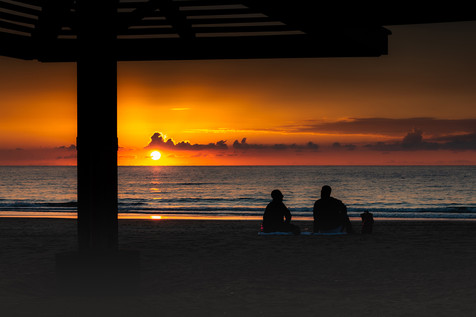 Two guys sit at the beach near the sea at sunset time