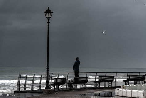 A man stands on a bench and looks at the sea
