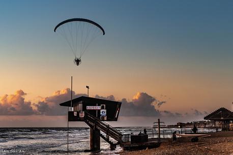 A parachutist at the beach at sunset time