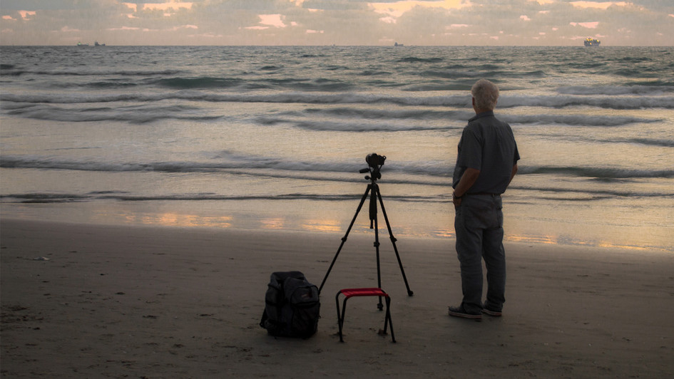 An old photographer at the beach at sunset time