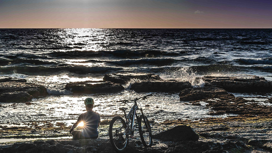 A guy with a bicycle sits at the beach at sunset time
