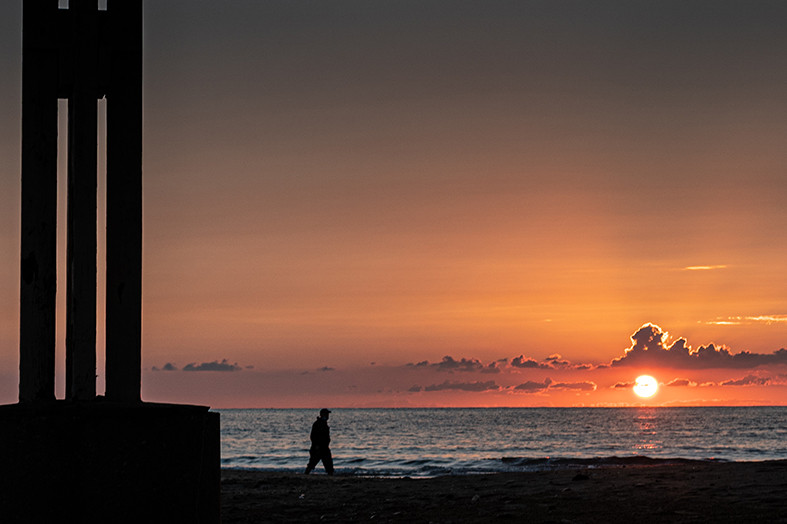 A man walks at the beach at sunset time