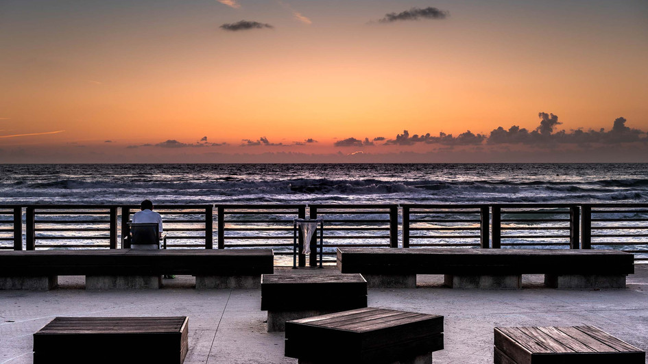 A man sits at a bench near the sea at sunset time