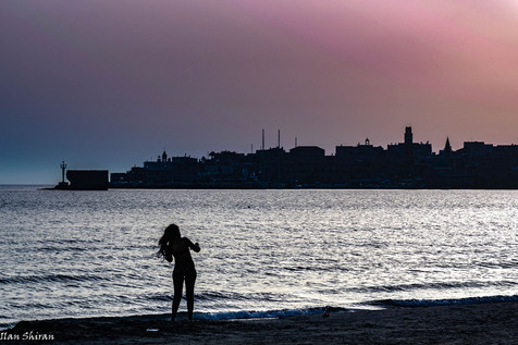 A woman stands at the beach at sunset time