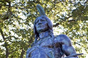 photo of Massasoit statue with green tree branches in background