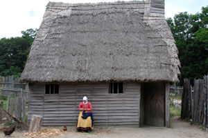 photo of a pilgrim woman sitting in front of a thatch roof house