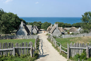 photo of Plimoth Plantation landscape houses and fences with ocean in background