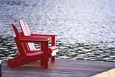 2 rote, niedrige Holzsessel auf einem Steg am Wasser