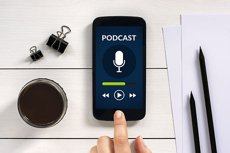 Podcast concept on smart phone screen with office objects on white wooden table. All screen content