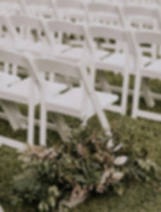 White folding chairs set up for wedding ceremony