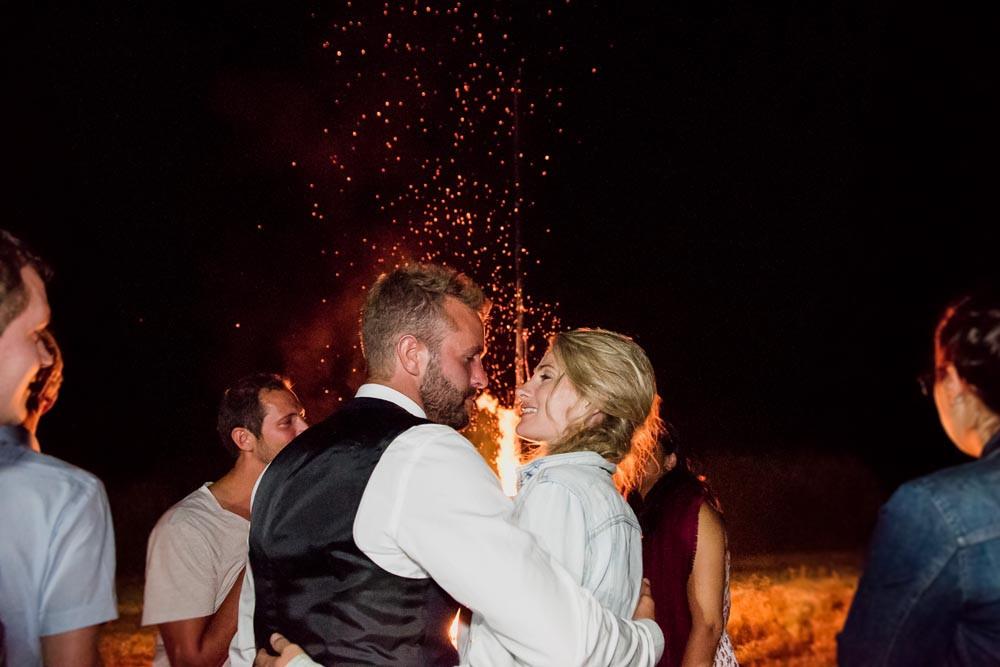 les mariés se regardent et s'embrassent devant l'immense feu allumé pour leur mariage