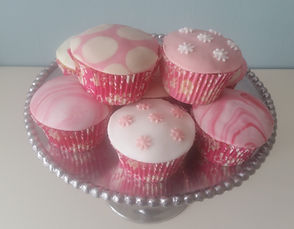 Selection of cupcakes with pink sugarpaste covering in various patterns.