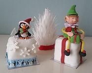 3 mini Christmas cakes with a sugar pengui and a sugar elf.