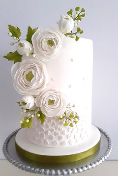 White double barrelled cake with sugar rannunculus flowers and leaves