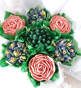 A Cupcake Bouquet of 7 cupcakes with piped buttercream flowers, wrapped in tissue and celophane