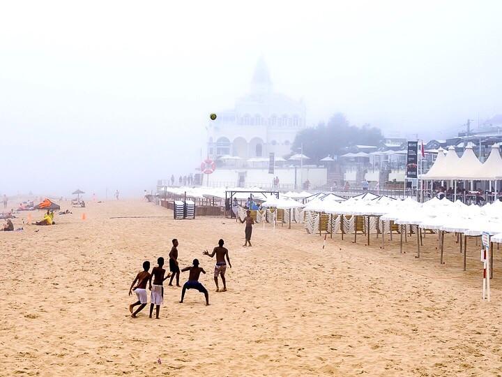Boys playing football on Estoril beach, Portugal