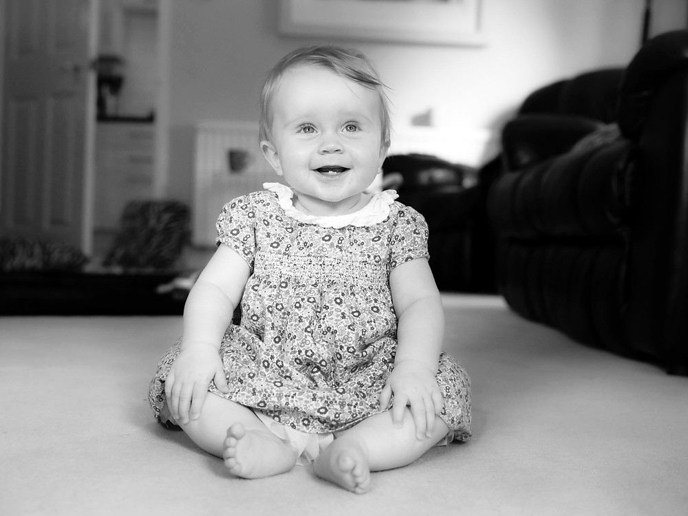 Fujifilm GFX picture of baby sitting on floor smiling