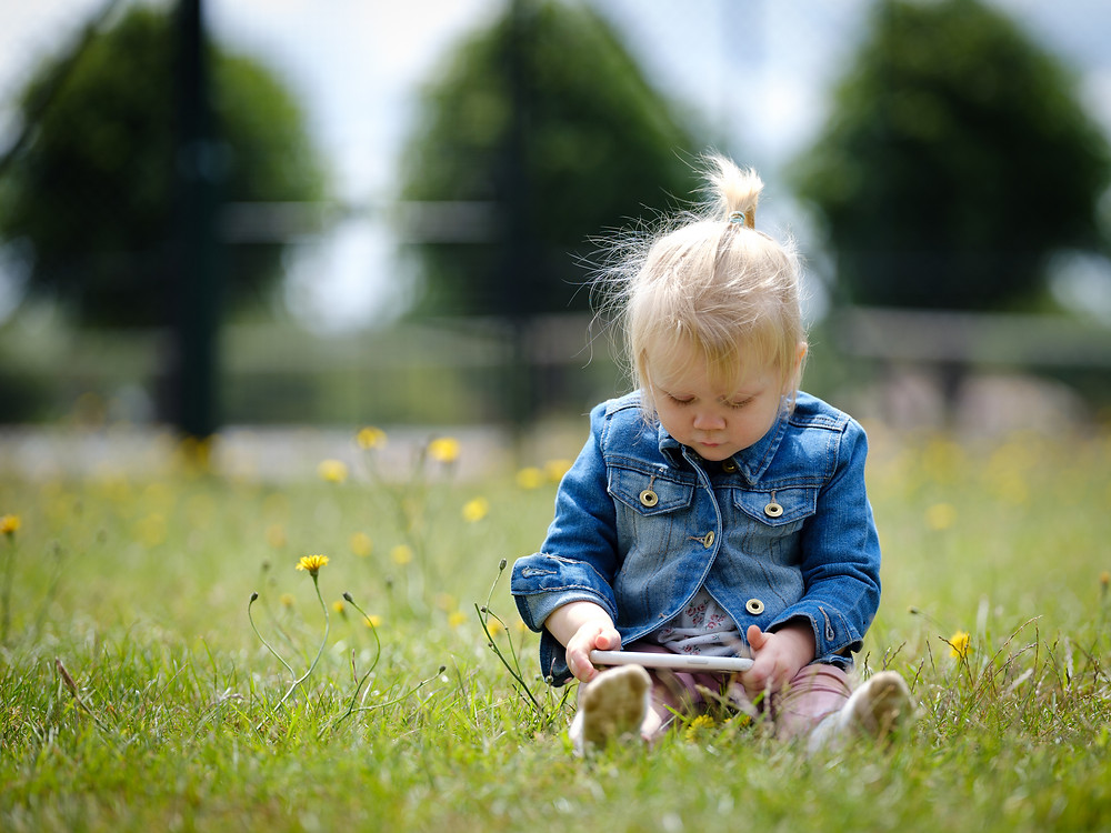 cute little girl sitting on grass intent on iPad
