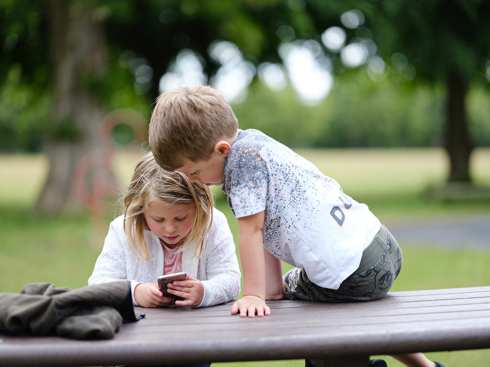 children looking intently at a mobile phone