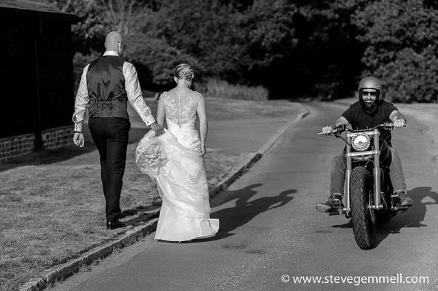 Funny shot of bride and groom plus passing motor cycle