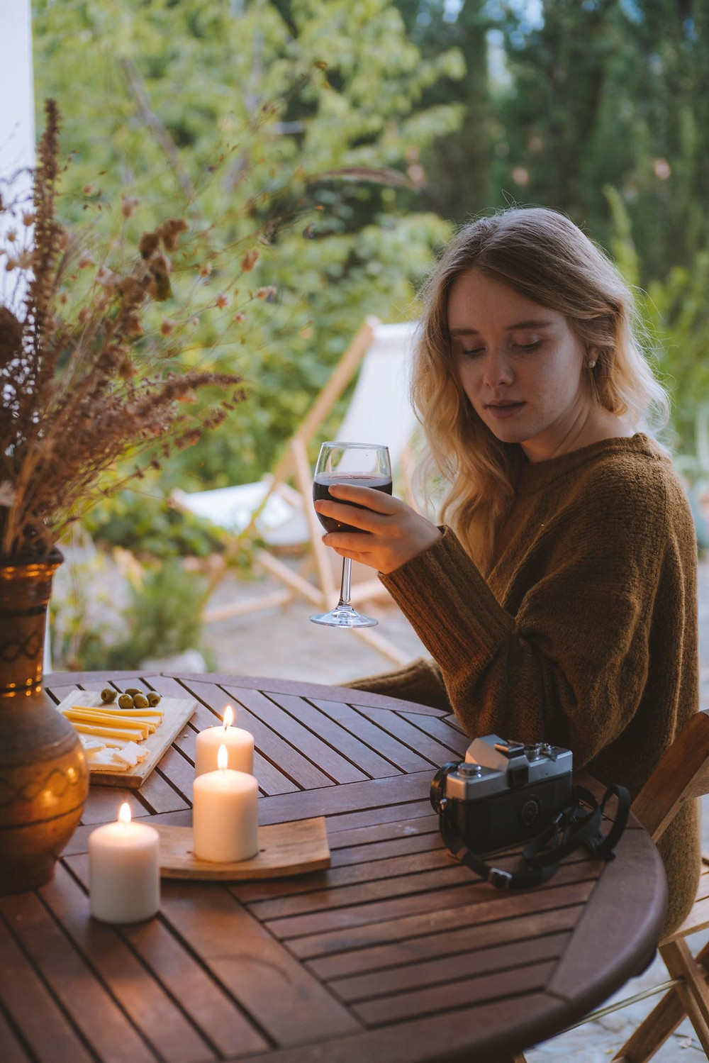 A girl drinking wine in the yard