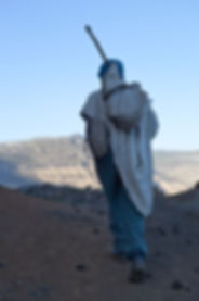 Ethiopian highlander man walking to his village, probably from a distance, since he got his lunch box and what he has to bring with him