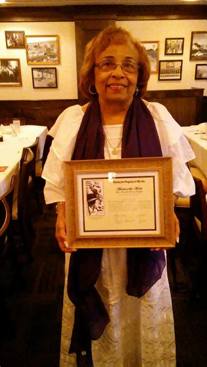 Women For Progress presents a certificate recognizing the 50th year anniversary of her historic election.