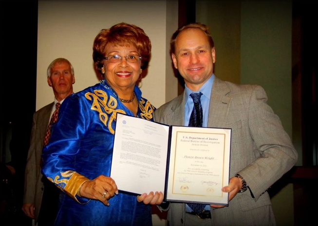 FBI agent Christopher Frieze presents Flonzie with certificate after graduating from the FBI Training Academy Class.