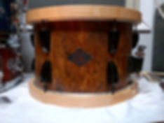 12x8 Maple shell with Mapa Burl veneer.  Maple hoops and black bow tie lugs.