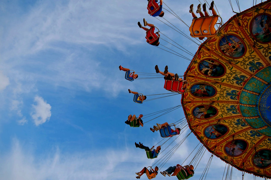 people on amusement park swings in the sky