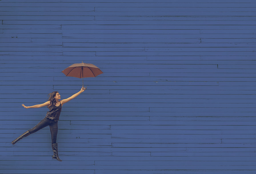 Girl dancing with umbrella next to a blue building