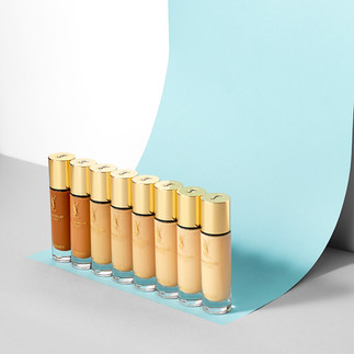 creative still life photography ysl foundations on a curved blue background