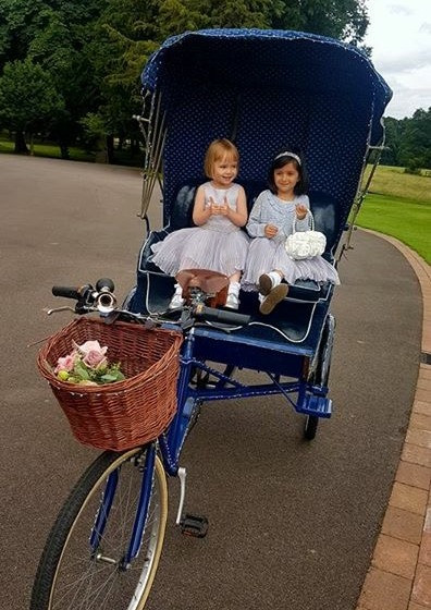 Rickshaw cycle and flower girls