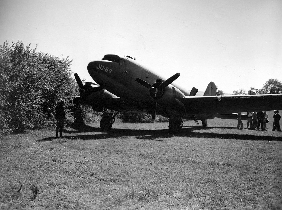 Emergency evacuation, 17. September '44, Koceljeva, near Valjevo, Serbia. The first C-47 to land ended up in the bushes at the end of the field.