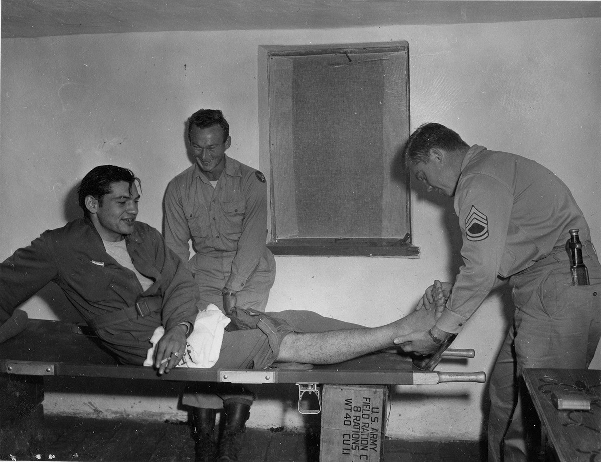 Capt. Joseph R. Scurzi being made ready for examination by (left) S/Sgt. James C. Reaves and (right) T/Sgt. W.C. McCrorey, assistants to Capt. J.H. Mitrani, MC 15th AAF Flight Surgeon, at the collecting center. Capt. Scurzi, co-pilot of B-17 (97th Bomb Group) shot down 22. July '44 on his 50th mission. Two motors shot out over Ploesti, finished off by Me-109. He and crew bailed at 1300ft over Suva planina. Picked up by Chetniks, kept 31 days at Studenja, then by truck thru Nis, Aleksinac, both towns were Gerry held. Stayed 10 days at Bocina, arrived at collecting center 4. Sept. '44 by cart because of broken foot received in landing. Evacuated nite of 4. Sept. '44.