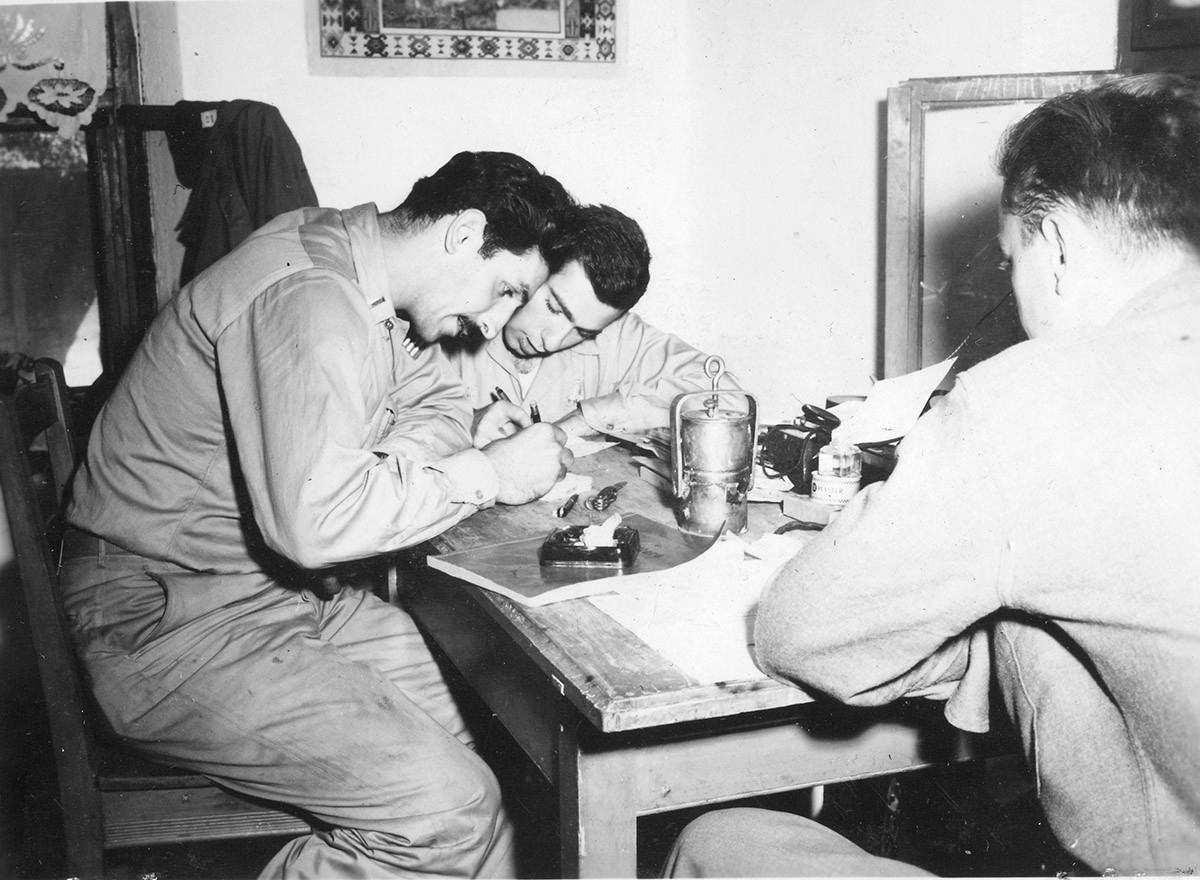 Three members of the Halyard team (OSS) preparing a radio message at our Hq. Left to right: Lt Nick Lalich, Arthur Jibilian, Mike Devyak. 29. Aug. '44.