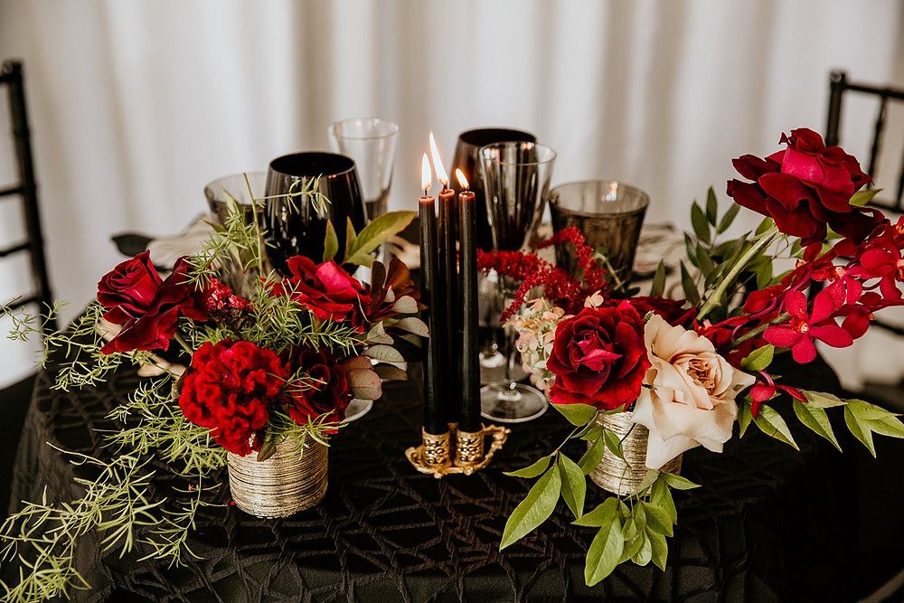 Red flowers and black candles tablescape
