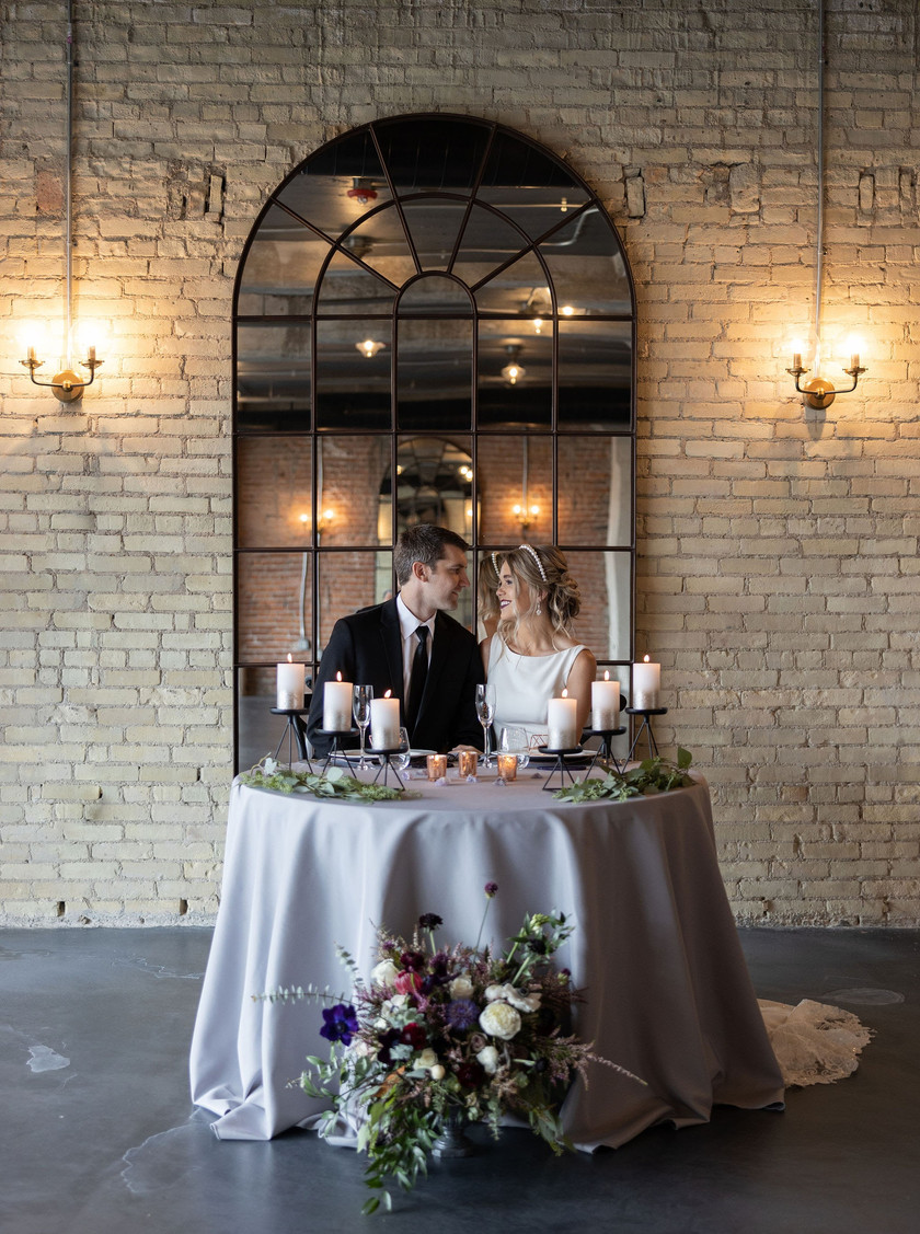 Couple with sweetheart table at wedding