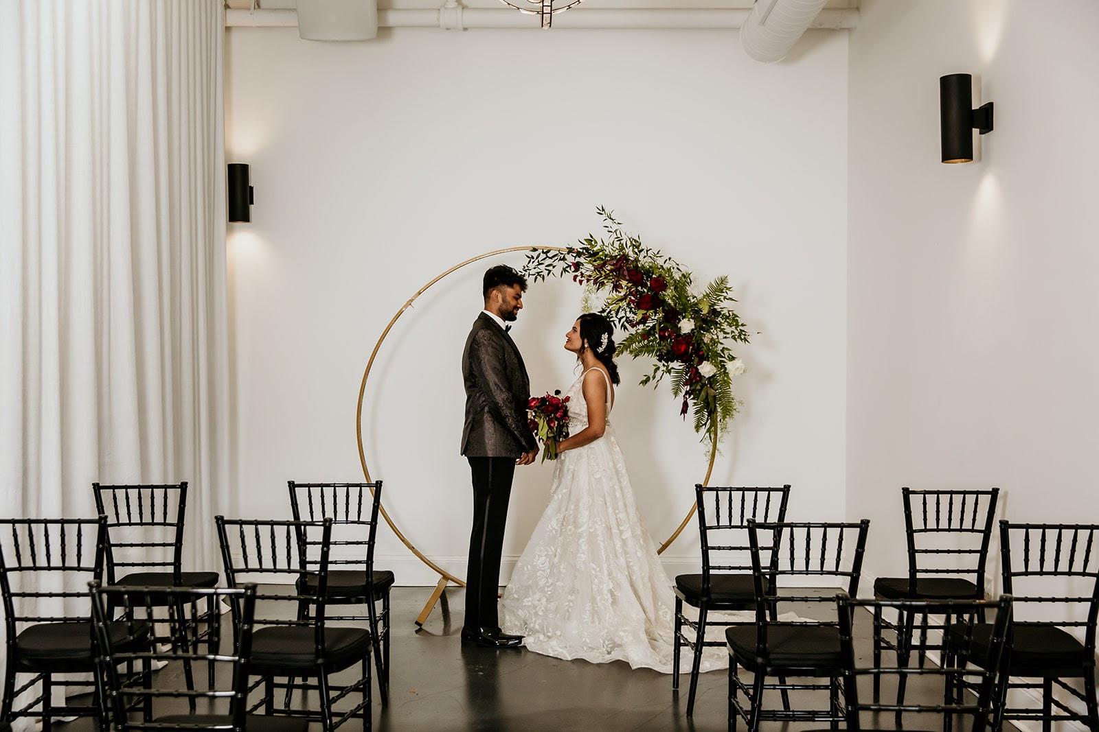 Indoor wedding ceremony with black chairs