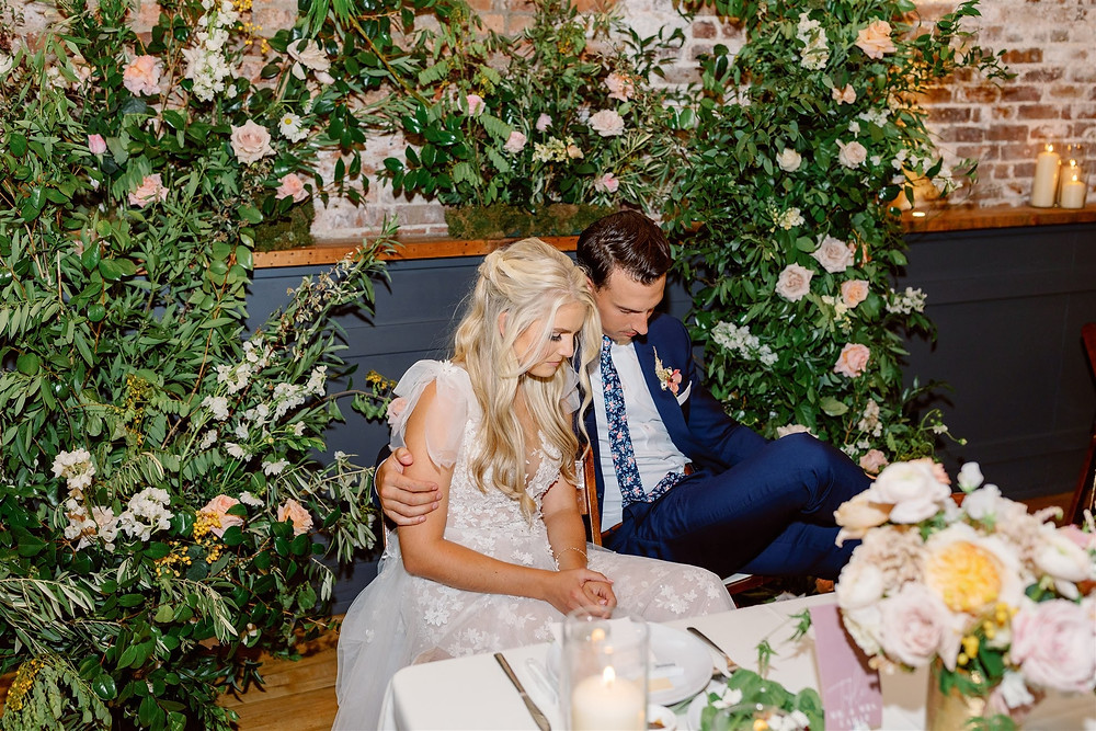 Sweetheart table with lush floral installation