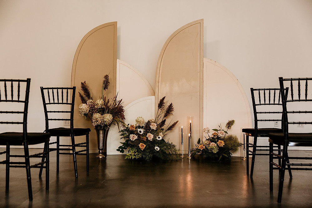 Fall wedding ceremony with arch backdrop
