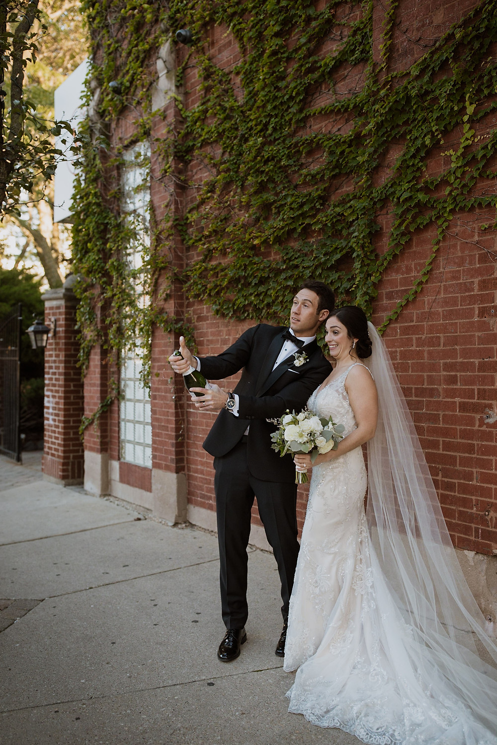 Couple popping champagne on their wedding day