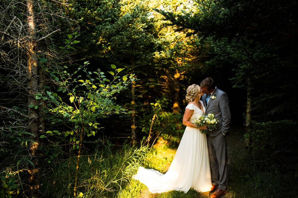 Bride and groom in woods at sunset