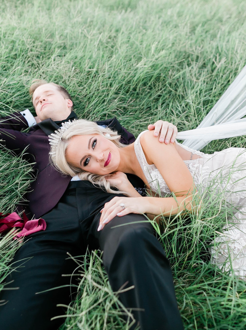 Bride laying on groom on wedding day