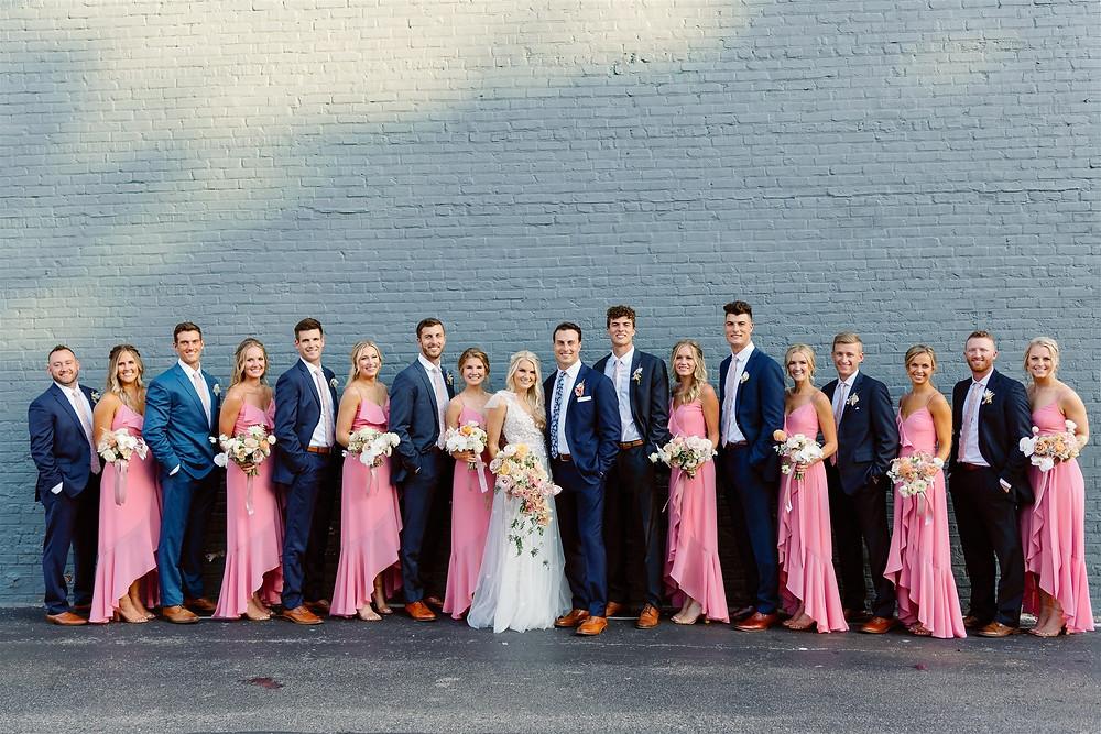 Bridal party against brick wall