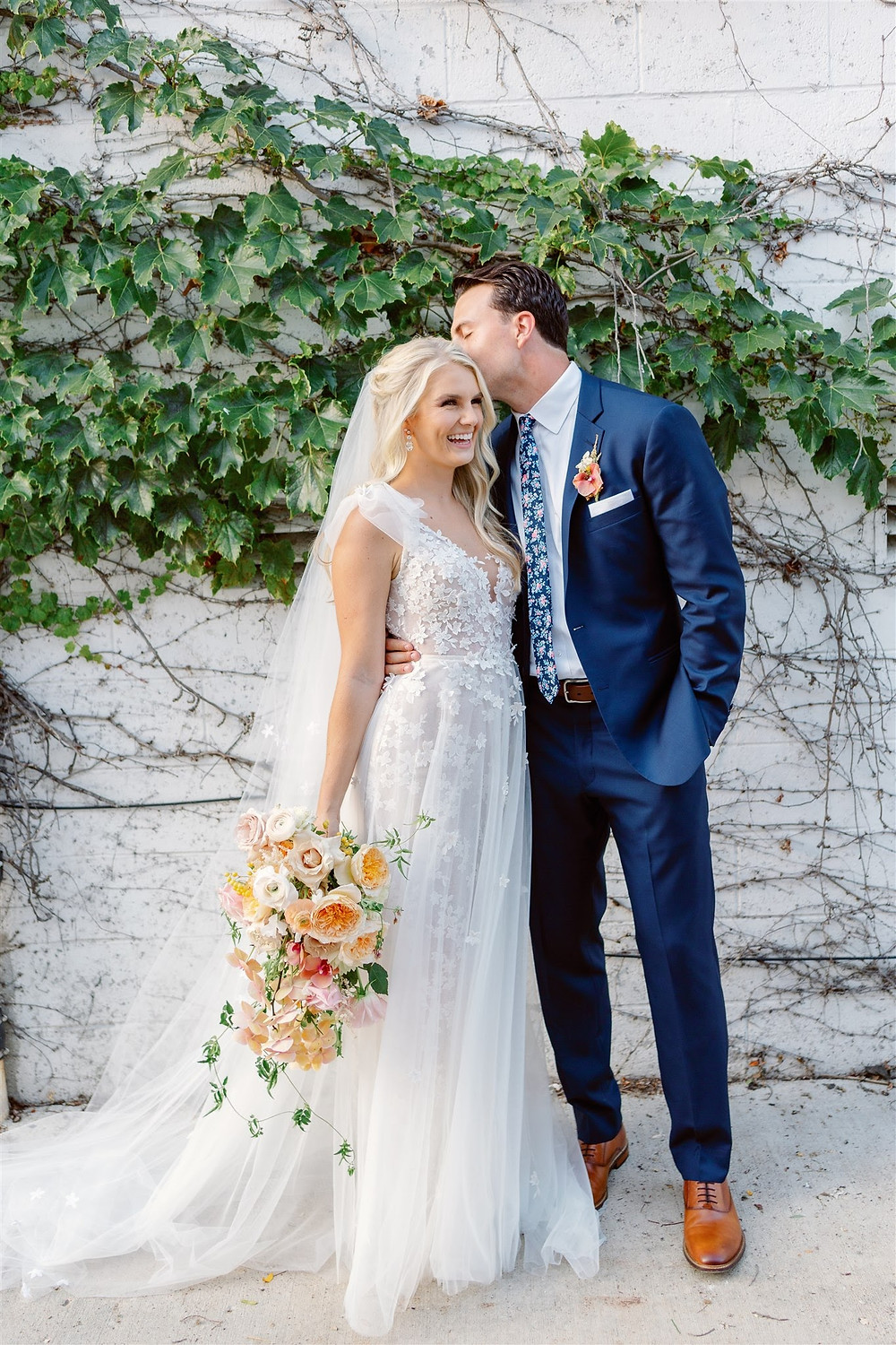 Bride and groom against ivy wall