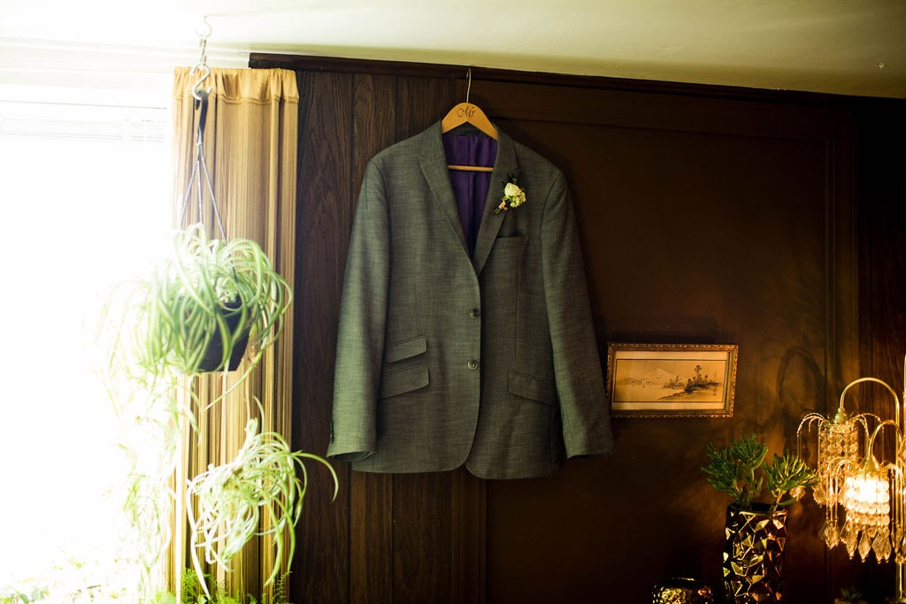 Groom's jacket hanging on wall