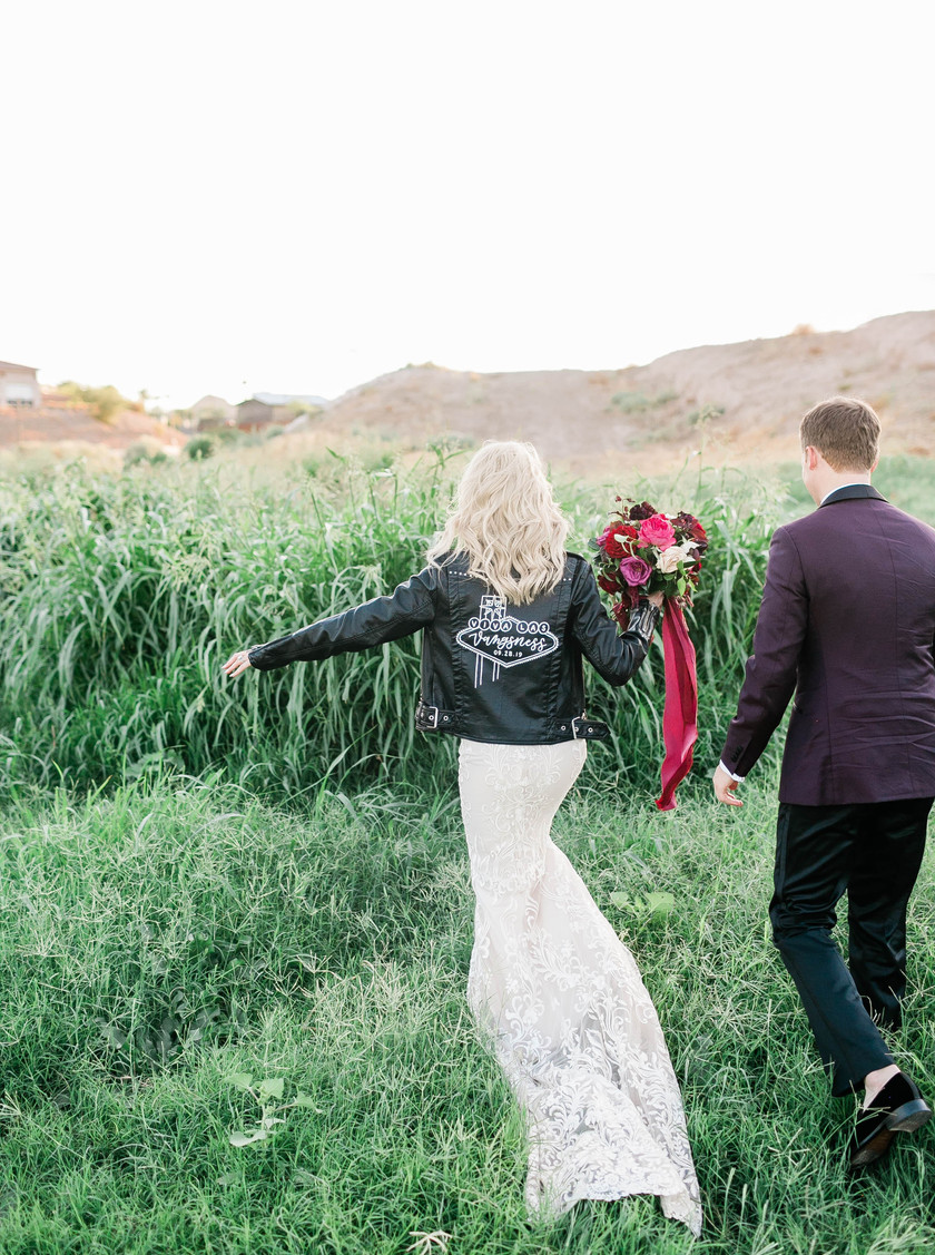 Bride in leather jacket with flowers